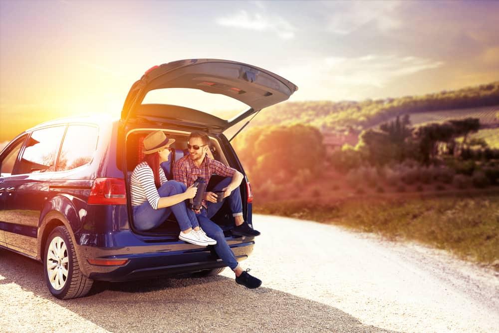 Ein Mann und eine Frau sitzen im Kofferraum eines Autos