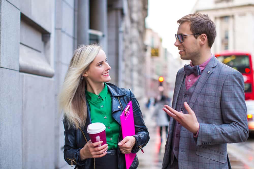 Ein Mann und eine Frau unterhalten sich auf der Straße, während sie Kaffee in der Hand hält