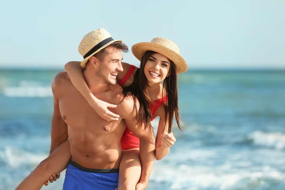 Ein glücklicher Mann trägt seine lächelnde Frau zum Strand