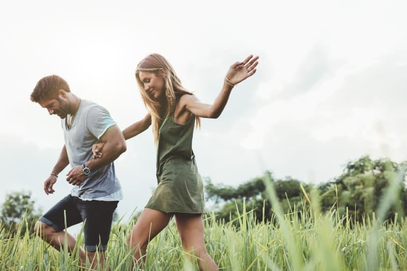 Ein junges Paar setzt sich ins Gras