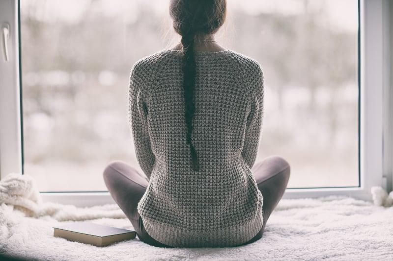 Ein junges einsames Mädchen sitzt allein am Fenster