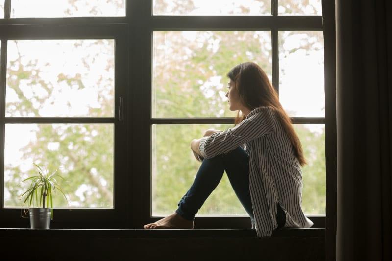 Ein junges nachdenkliches Mädchen sitzt am Fenster