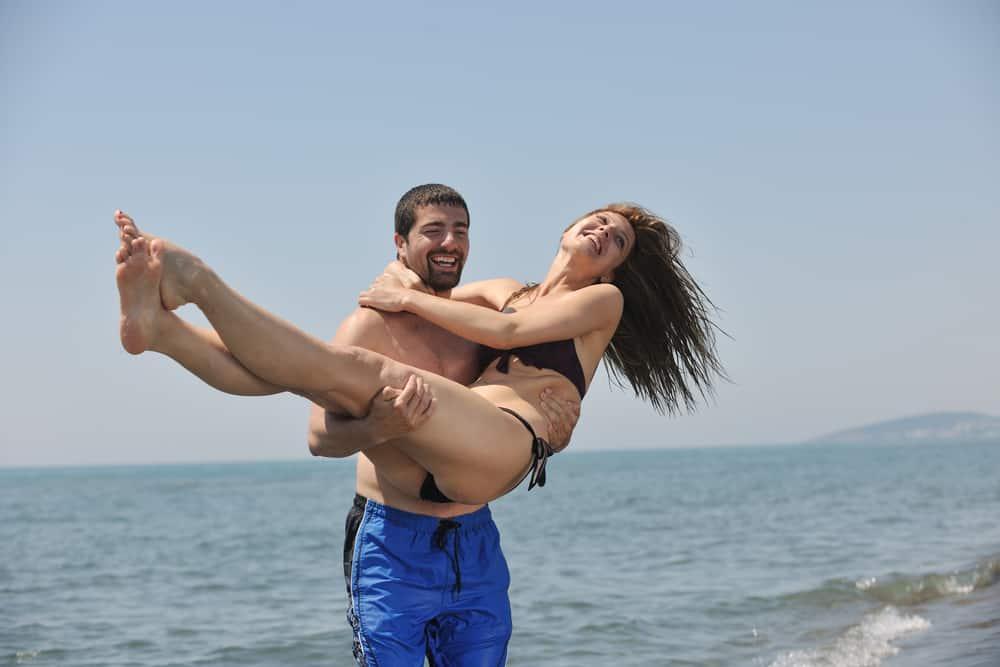Ein lächelnder Mann trägt seine glückliche Frau in seinen Armen aus dem Meer