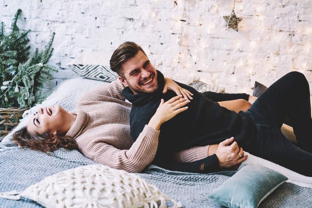 Ein lächelnder Mann und eine lächelnde Frau liegen auf einem Doppelbett