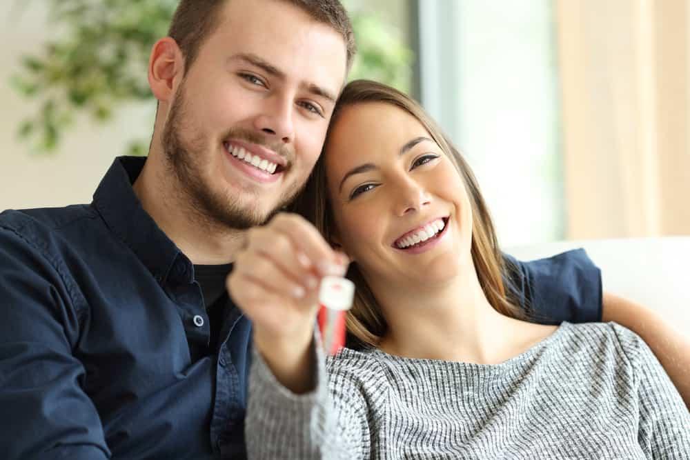 Ein lächelndes Mädchen mit Schlüsseln in der Hand sitzt neben ihrem zufriedenen Mann