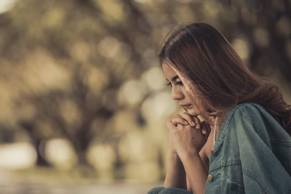 Ein sehr trauriges Mädchen sitzt draußen und denkt nach