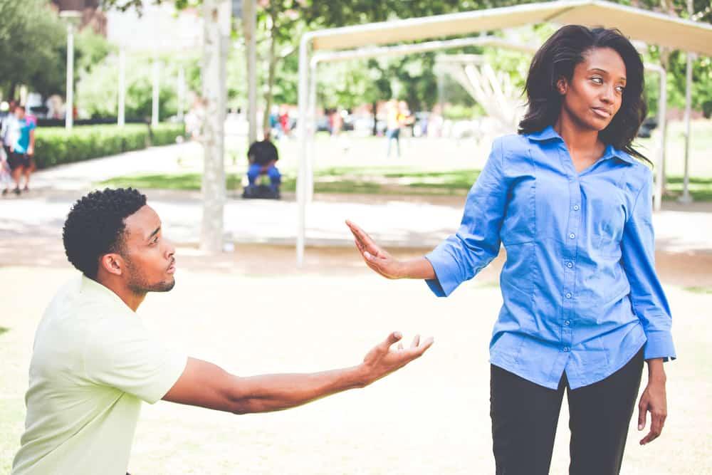 Ein trauriger Mann auf den Knien bittet eine Frau, ihm zu vergeben