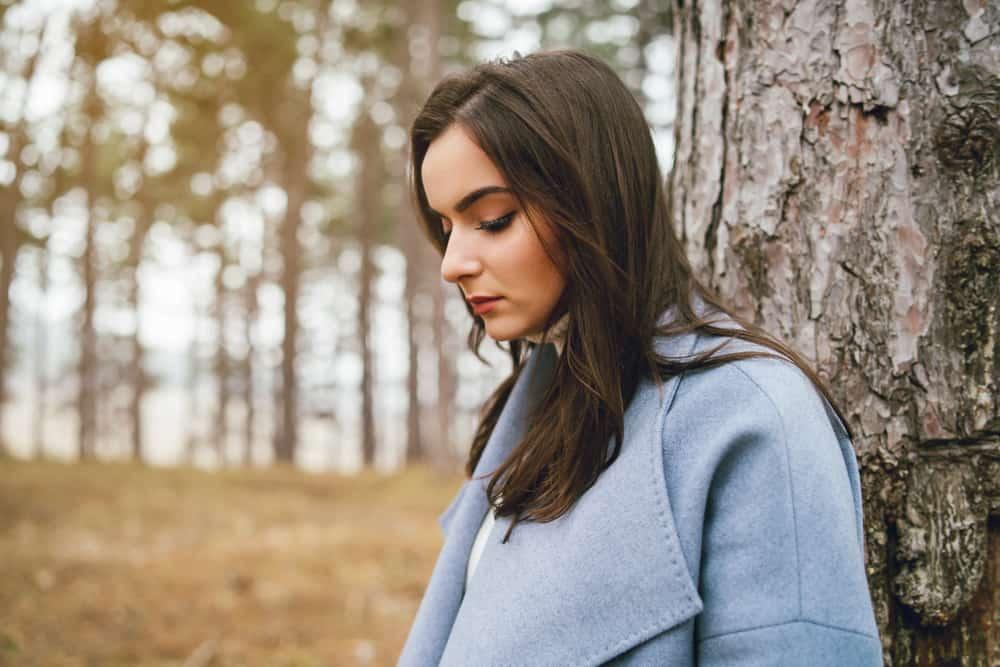 Eine Brünette in einem blauen Mantel steht neben einem Baum im Wald