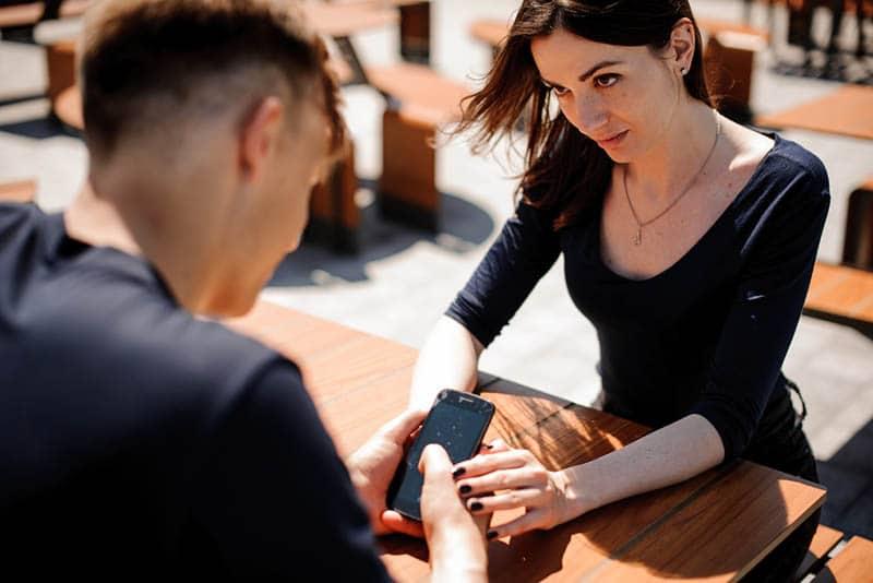 Frau, die Mann betrachtet, während er seine Hand im Straßencafé hält