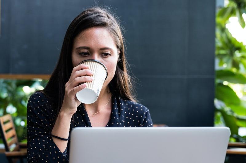 Frau gegenüber Laptop beim Halten der Einwegschale
