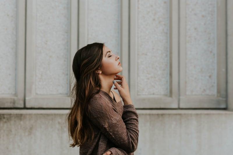 Frau in braunem langärmeligem Oberteil, das neben Wand steht