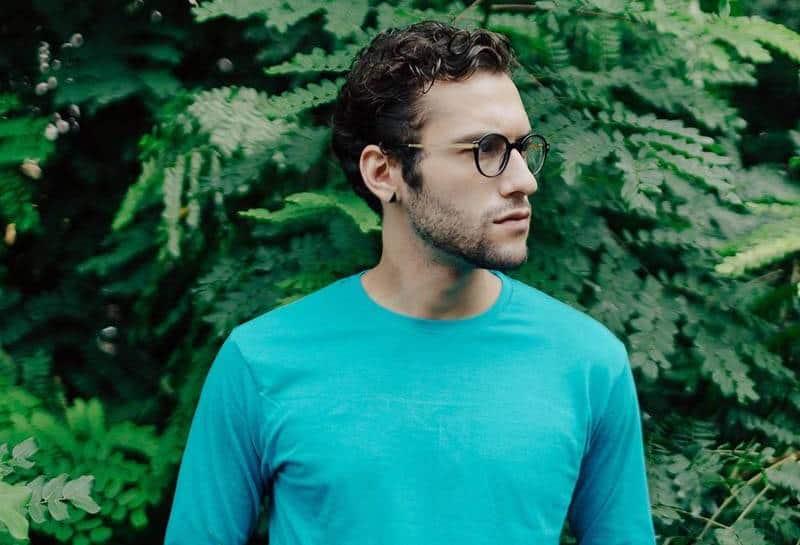 Mann mit Brille und blauem Langarmhemd, das draußen steht