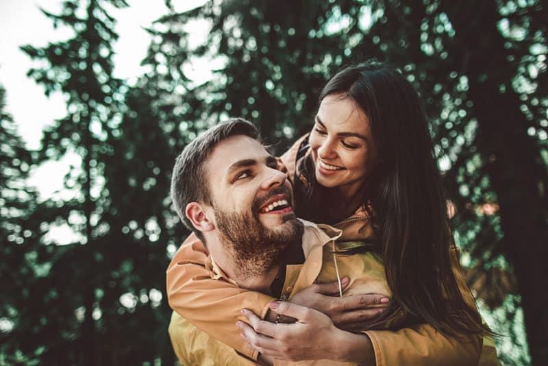 Mann mit glücklicher Frau auf dem Rücken