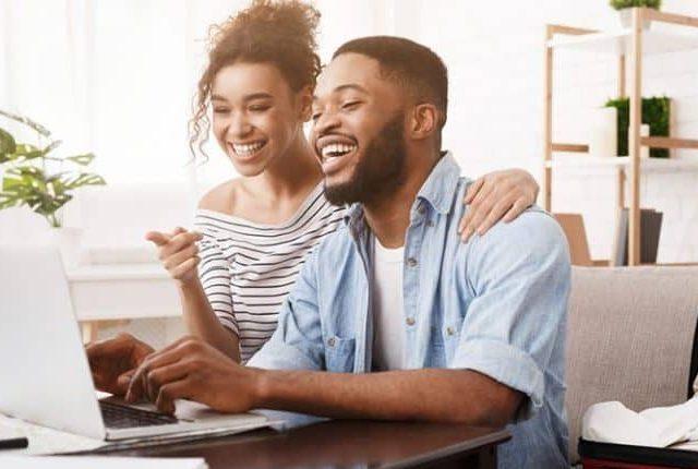 Mitarbeiter lachen und arbeiten am Laptop