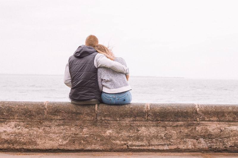 Paar sitzt auf braunem Betonpflaster
