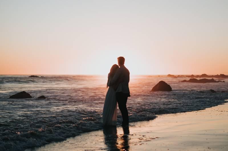 Schattenbildfoto des Paares, das am Strand steht und Sonnenuntergang beobachtet