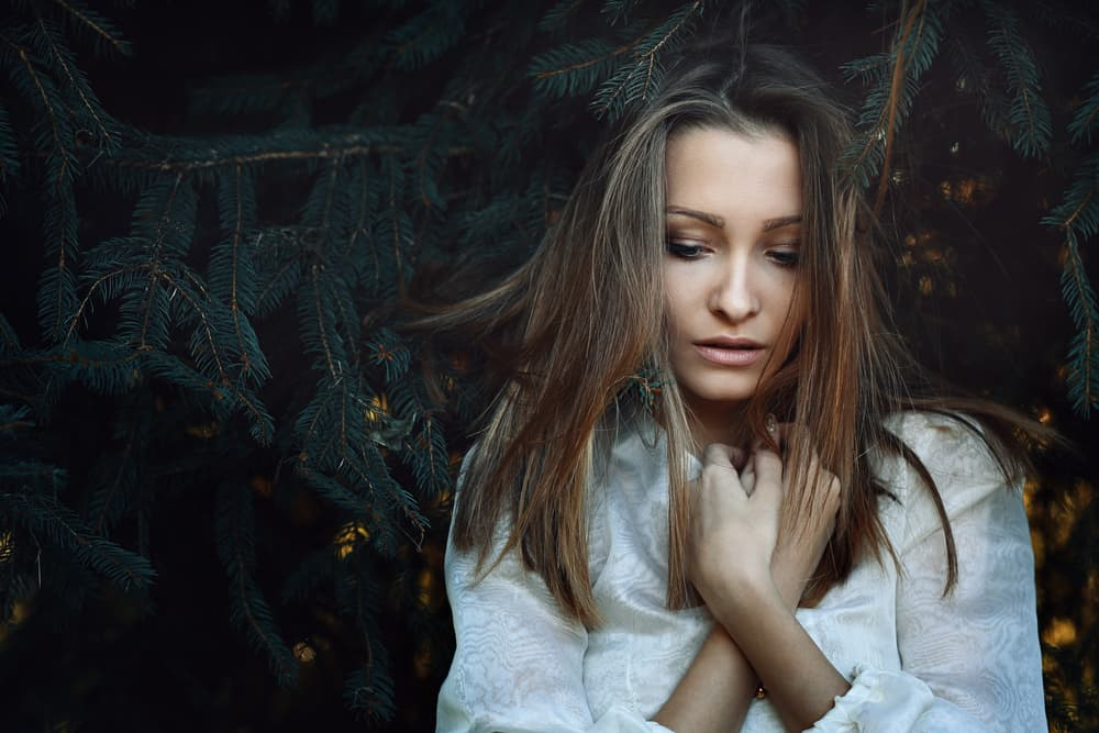 Unter den Kiefern steht ein schönes trauriges Mädchen im Bademantel