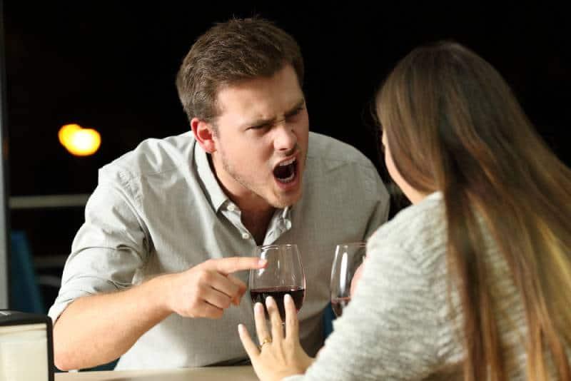 Wütendes Paar, das nachts in einer Bar wütend streitet