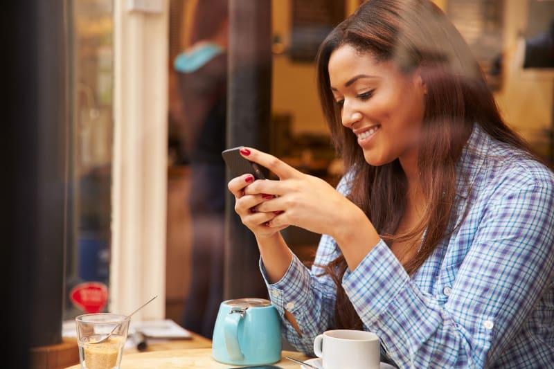 eine junge Frau, die alleine in einem Café sitzt und einen Schlüssel auf ihrem Handy hat