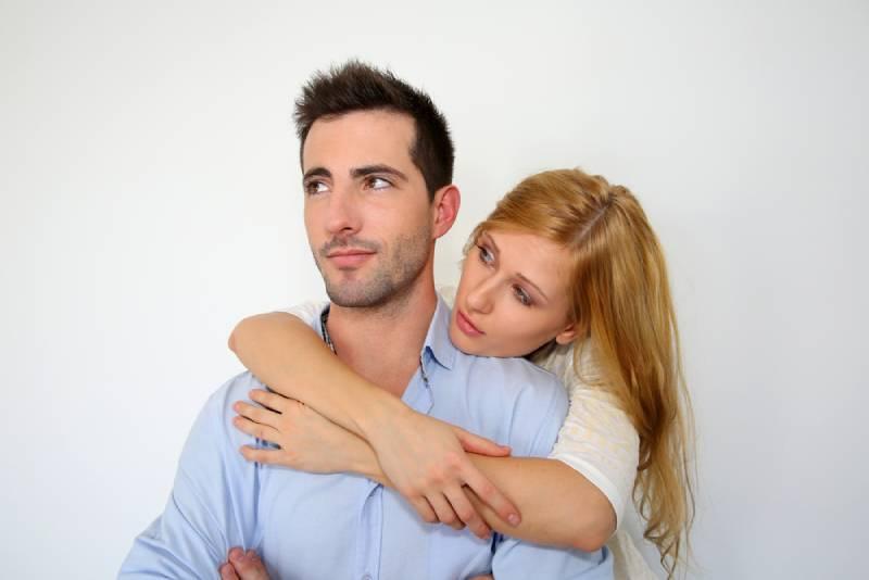 Frau umarmt nachdenklichen Mann