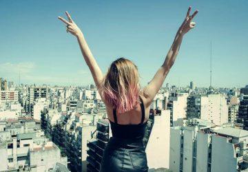 das Mädchen oben im Gebäude mit ausgestreckten Armen