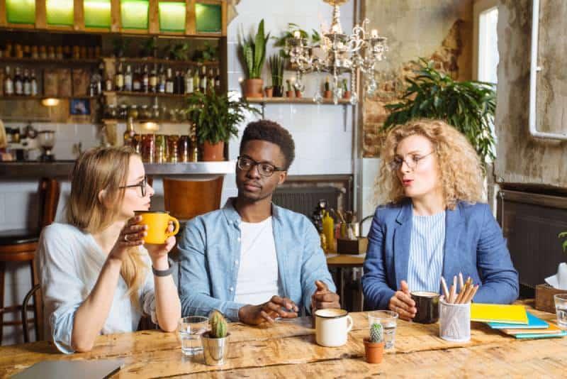 Zwei Frauen, ein Mann, der im Café spricht