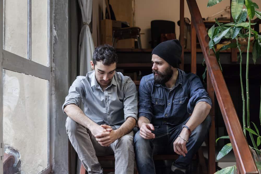 Zwei Männer unterhalten sich auf der Treppe
