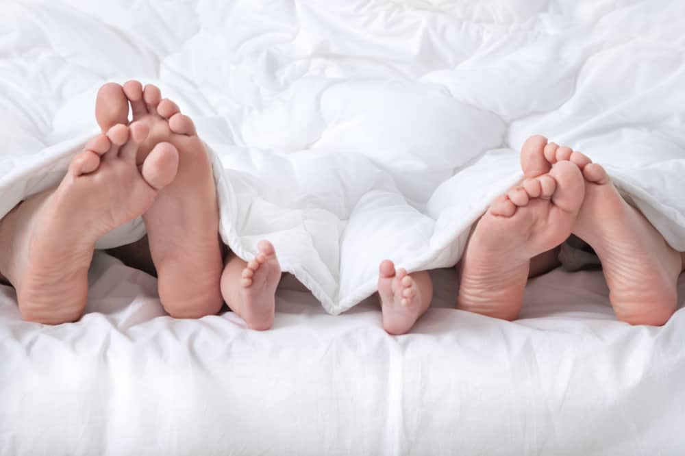 die Beine eines Mannes, einer Frau und eines Babys unter einer weißen Decke