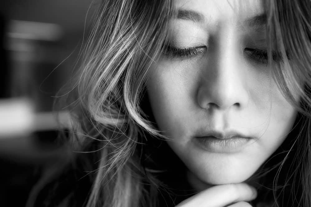 ein Porträt einer traurigen Frau mit geschlossenen Augen