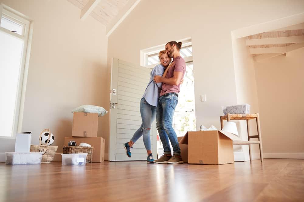 ein glückliches Paar, das in einer unmöblierten Wohnung mit Pappkartons steht