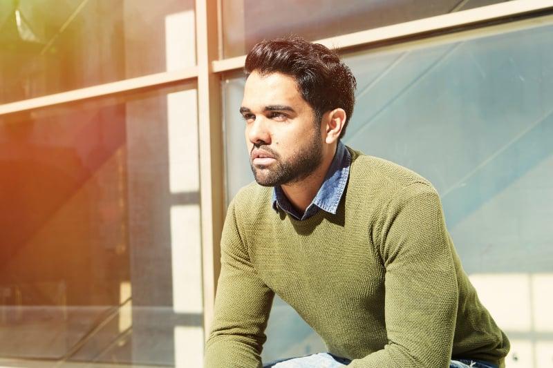 ein hübscher Mann, der auf einer Bank sitzt
