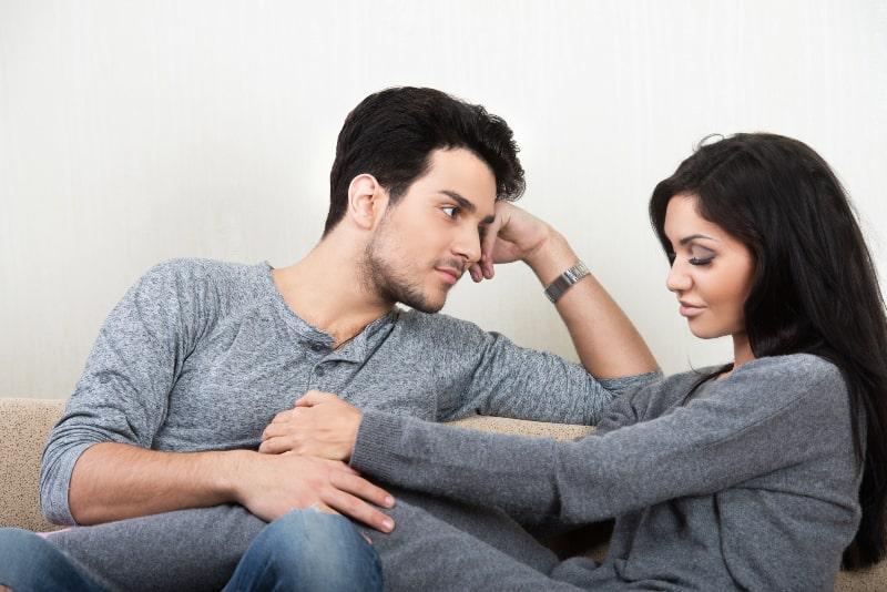 ein junges Paar spricht auf der Couch