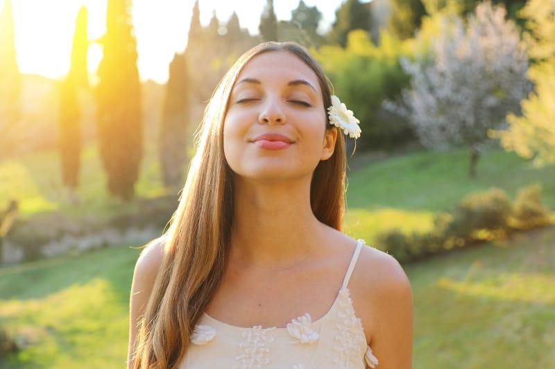 ein junges glückliches Mädchen mit geschlossenen Augen