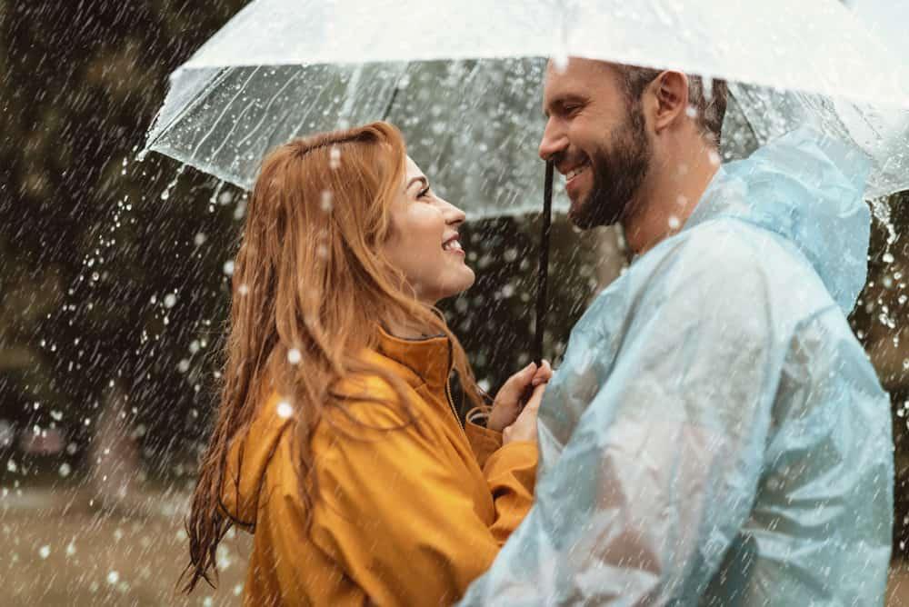 ein lächelndes Paar im Regen unter einem Regenschirm