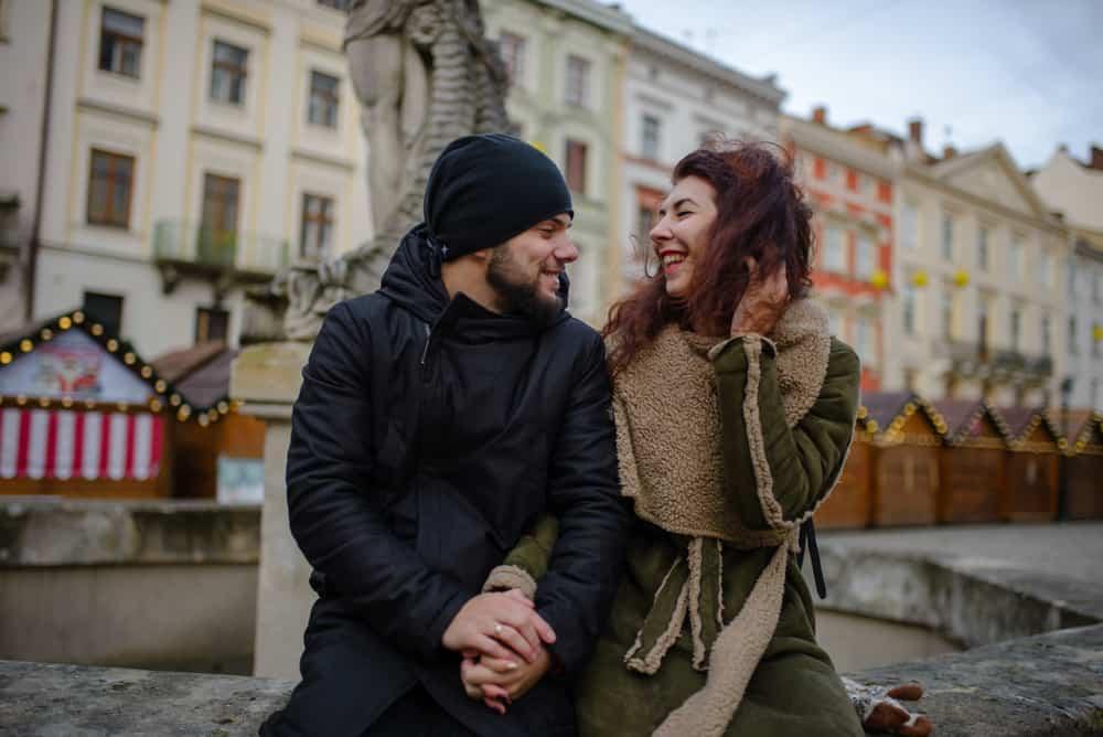 ein verliebtes romantisches Paar, das draußen auf den konkreten Händchen haltend sitzt