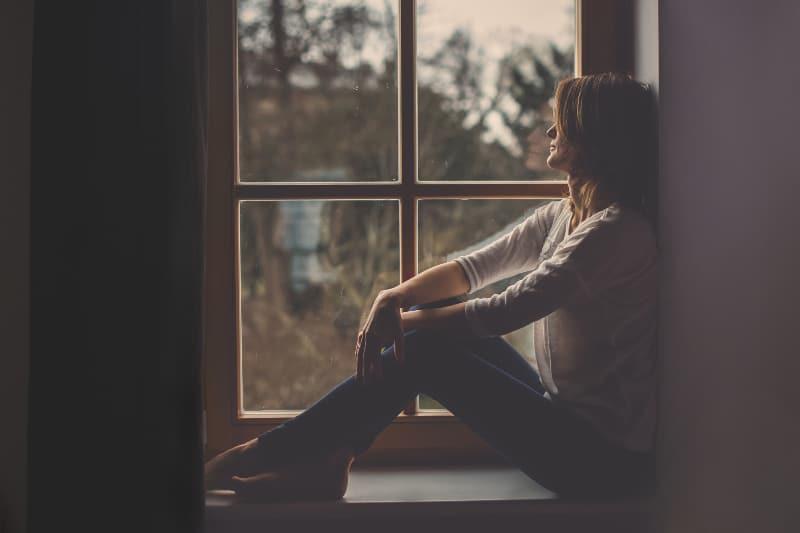 eine junge attraktive Frau, die am Fenster sitzt