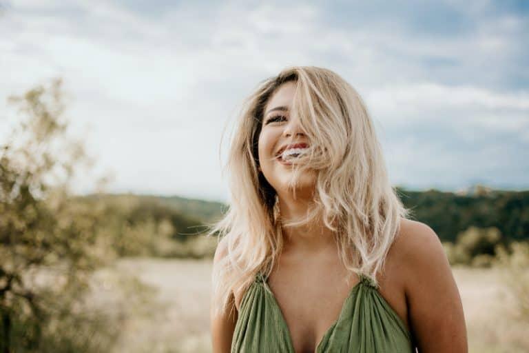 eine lächelnde Blondine in einem Kleid