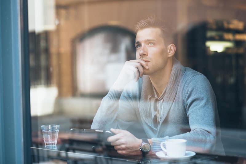 ernsthafter junger Mann, der im Café denkt