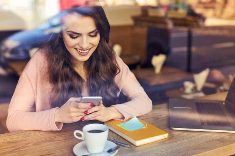 lächelnde Frau, die auf ihrem Telefon im Café tippt