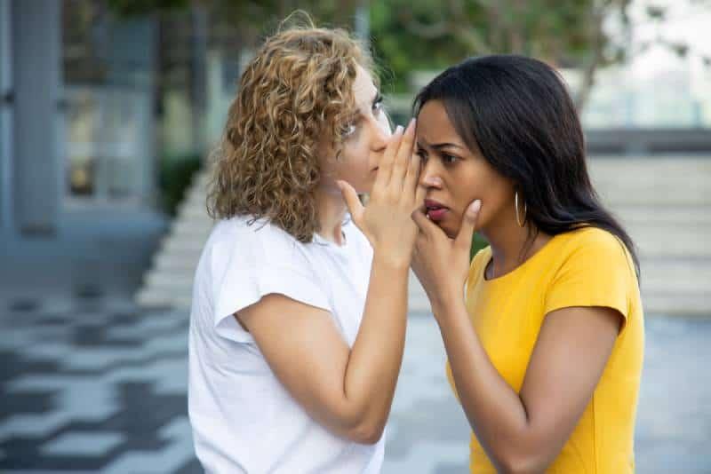 weiße Frauen klatschen und flüstern der schwarzen Frau draußen zu