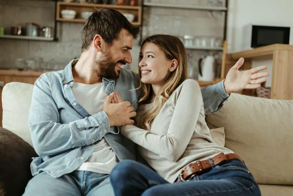 Auf der Couch sitzt ein lächelndes Paar in einer Umarmung und redet