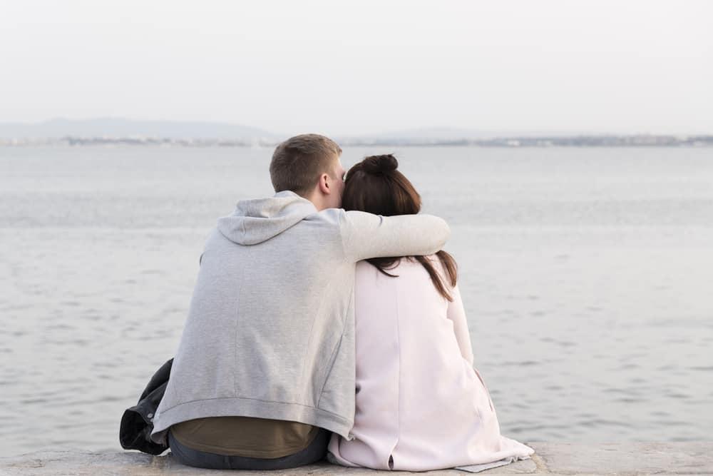 Ein Mann am Strand sitzt und umarmt seine Frau fest