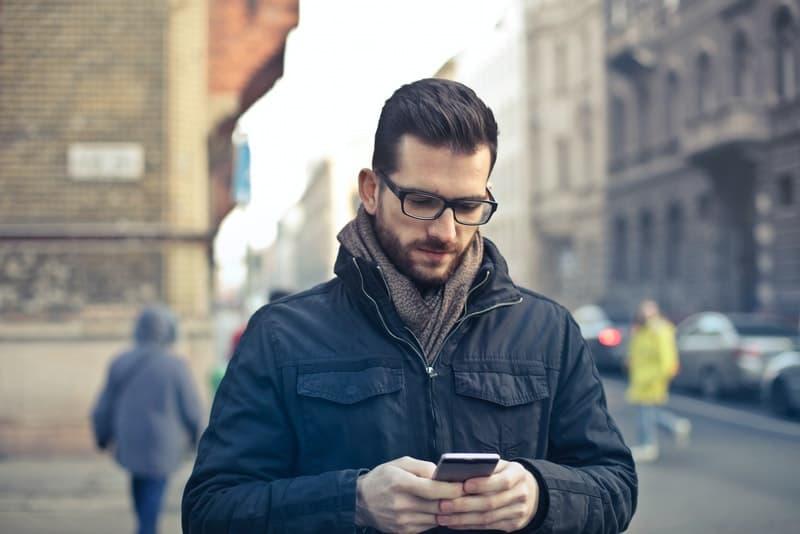 Ein Mann mit Brille und schwarzer Jacke schreibt eine Nachricht auf sein Handy