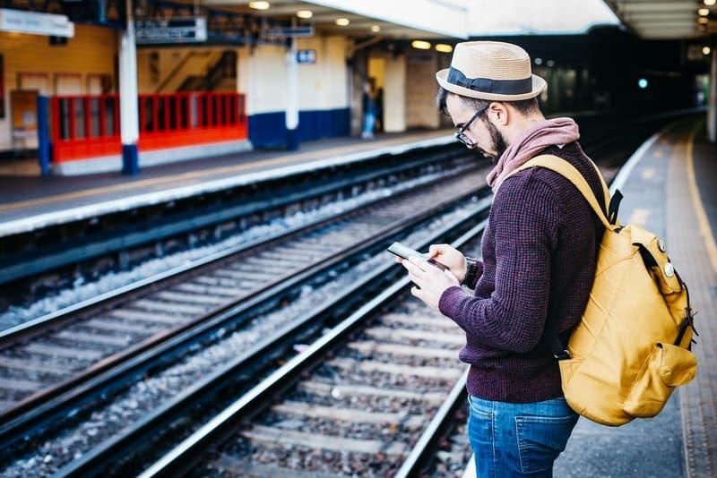 Ein Mann mit einem Hut auf dem Kopf an einem Bahnhof benutzt ein Handy