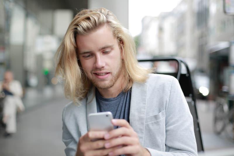 Ein Mann mit langen blonden Haaren schreibt eine SMS