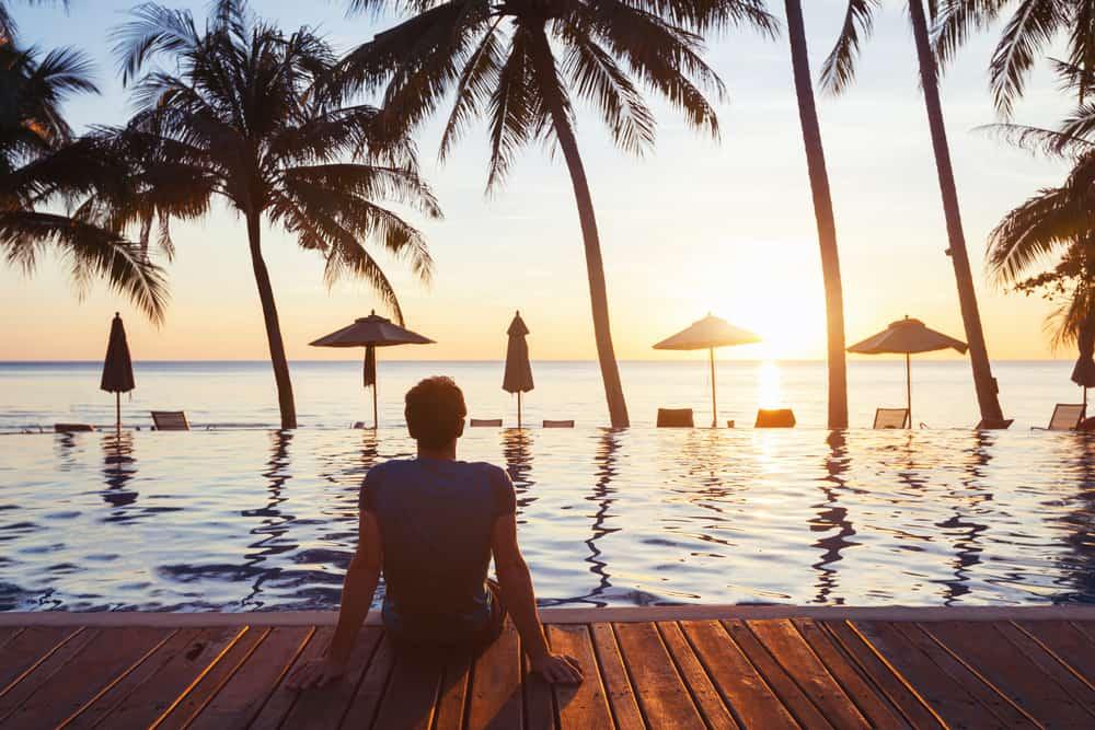 Ein Mann sitzt auf dem Pier des Meeres und beobachtet den Sonnenuntergang