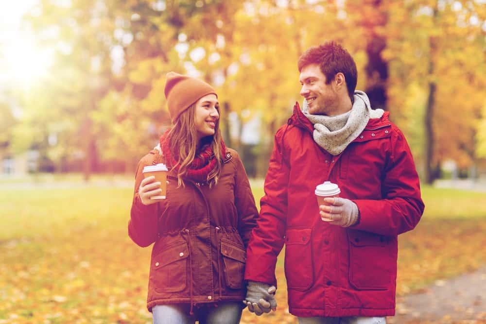 Ein liebevoll lächelndes Paar geht durch den Park