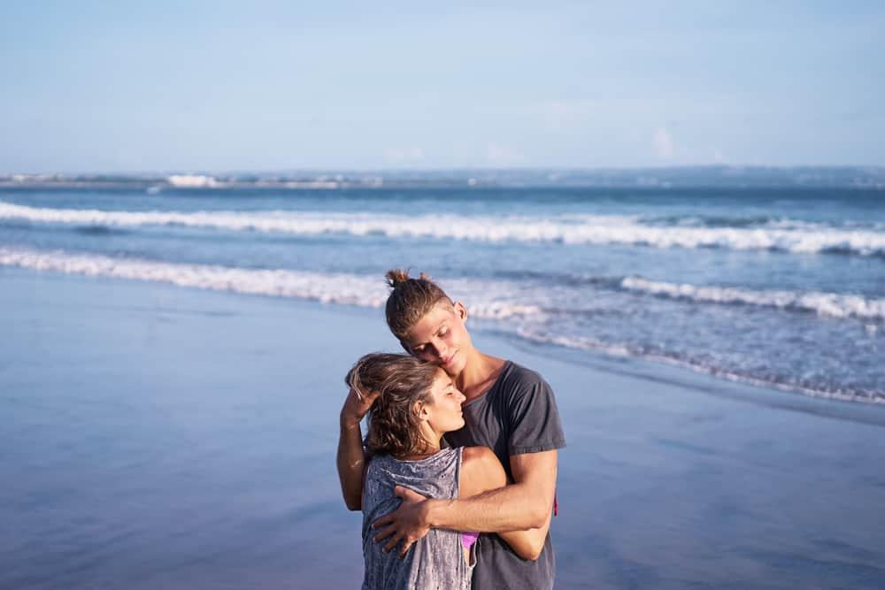 Ein liebevolles Paar in einer Umarmung steht am Meer