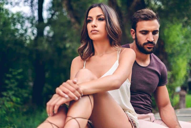 Ein trauriges Paar, das im Park sitzt und nachdenkt