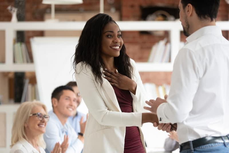 Eine junge schwarze Frau gibt einem Arbeitskollegen die Hand